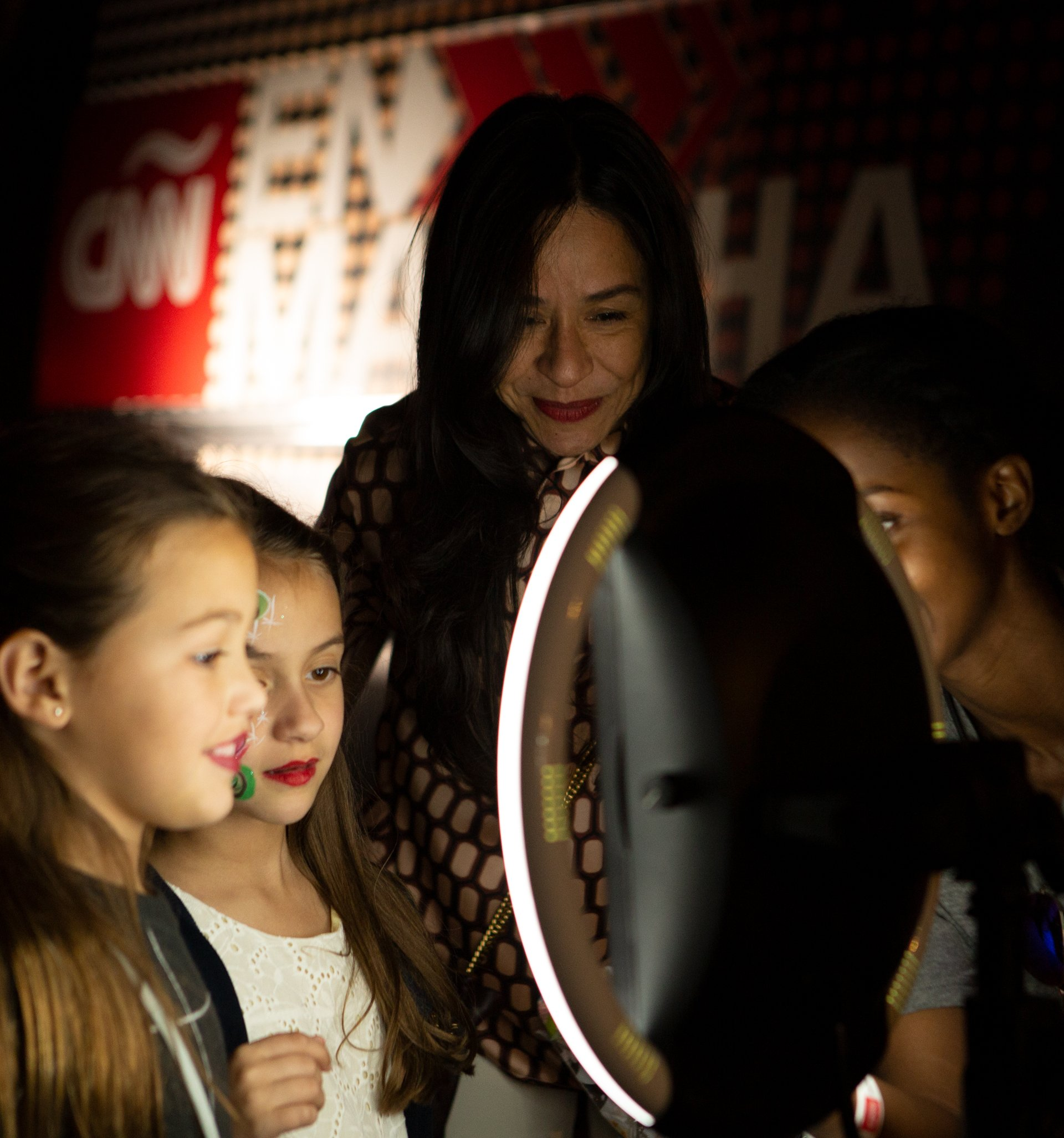 Young girls take a picture with the CNNE Twitter Mirror while mom is watching.
